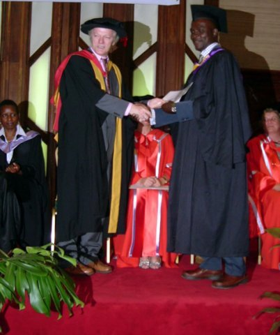 MA graduant receiving a certificate from Dr. William West